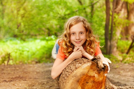 girl scout: Portrait of beautiful young girl laying on the log in summer forest