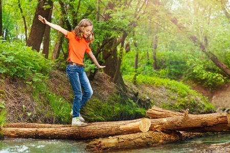 Portret van het leuke tiener in evenwicht brengen terwijl het kruisen van een logboekbrug over de bosrivier