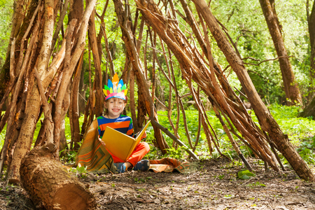 boy scouts tent: Happy boy in Red Indians costume reading blanked book, sitting in wigwam in the forest
