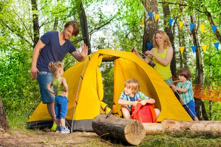 pitching: Happy young family, parents and three kids, pitching up a tent together in the forest