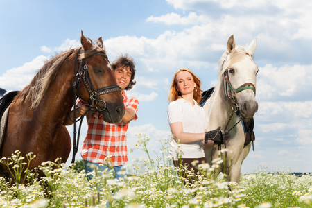 Portrait of young happy couple with their purebred horses in flowery meadows Stock Photo