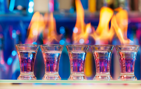 intoxicant: Five shot glasses with flaming cocktails standing in a row on a bar counter
