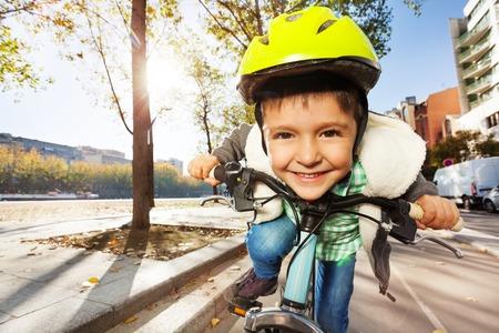 Close-up portret van schattige glimlachende jongen in gele helm rijden zijn fiets bij zonnige dag