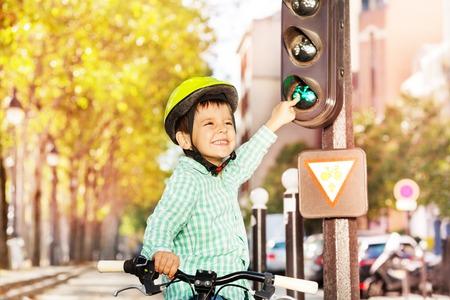 Glimlachende jongen fietsen op zijn fiets en leren verkeersregels in de stad, wijzend op groen signaal van lichten