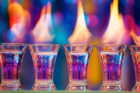 Close-up picture of hot shot glasses standing in a row on a bar counter