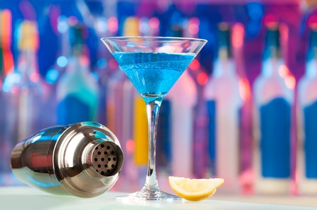 Picture of martini glass, lemon slice and empty shaker on a bar counter with copy-space