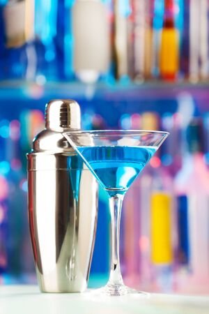 intoxicant: Close-up picture of martini glass filled with blue liquor and shaker standing on a bar counter