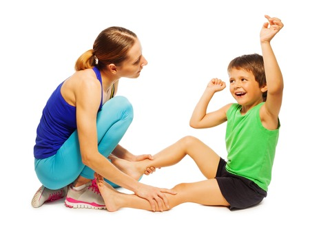 autistic: Portrait of happy kid boy sitting on the floor and doing physical exercises with female trainer, isolated on white Stock Photo