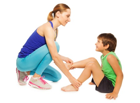 boy kid: Side view portrait of female trainer helping kid boy making gymnastics, isolated on white Stock Photo