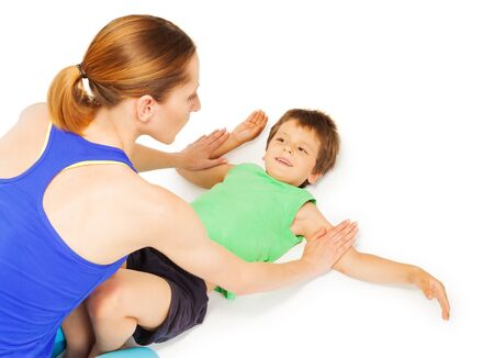 Happy kid boy exercising laying flat on back with his mother, isolated on white background