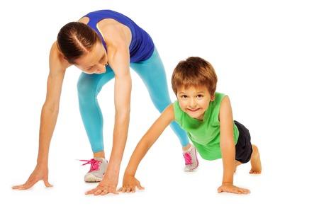 gimnasia aerobica: madre deportiva que hace empuje ups con su hijo niño, aislado en blanco Foto de archivo