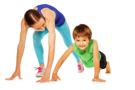 Sporty mother doing pushing ups with her kid son, isolated on white Stock Photo