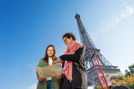 tourist guide: Bottom view portrait of two smiling tourists holding a paper map of Paris and searching right direction