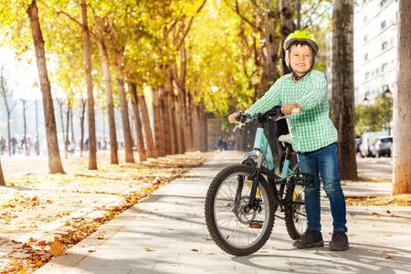 Portrait of smiling boy standing on cycle lane with his bike at autumn park Stock Photo