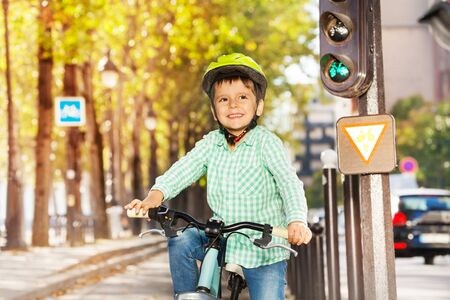 Cute boy in safety helmet riding his bike on green signal of traffic light