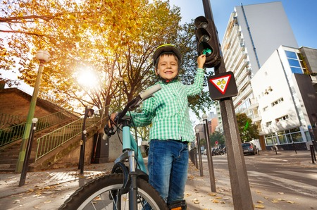 Five years old boy standing with his bike next to traffic light and pointing to green signal for cyclists Stock Photo
