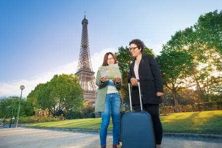 map case: Two happy female travelers with their trolley case, reading map against the Eiffel Tower in Paris