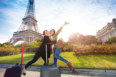 Two happy friends, female tourists, meeting in Paris near the Eiffel Tower 写真素材