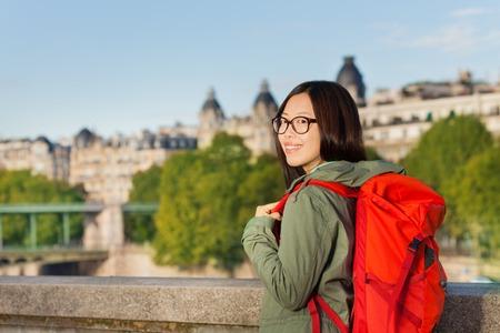 mochila de viaje: La muchacha asiática joven que recorre a lo largo de orilla del río Sena con morral rojo grande