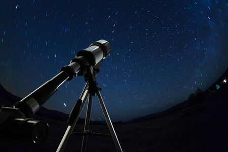stargazing: Telescope pointed to the clear night sky and stars Stock Photo