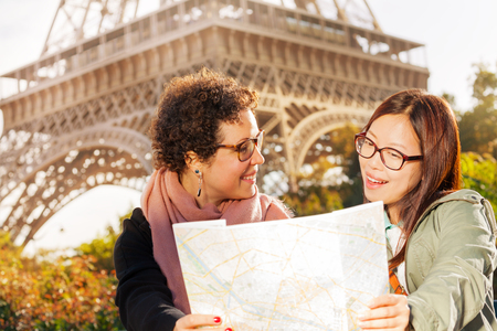 tourist guide: Two happy women with a paper tourist map in Paris Stock Photo
