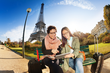 luggage travel: Two tourists sitting against the Eiffel Tower