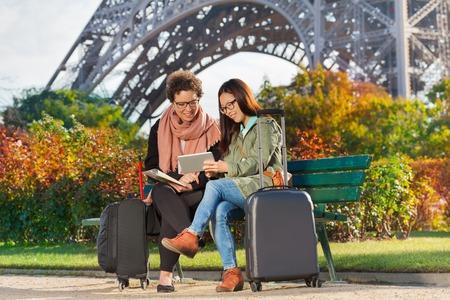 Travelers sitting on a bench near the Eiffel Tower Standard-Bild