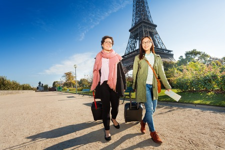 Two tourists walking around Paris with luggage