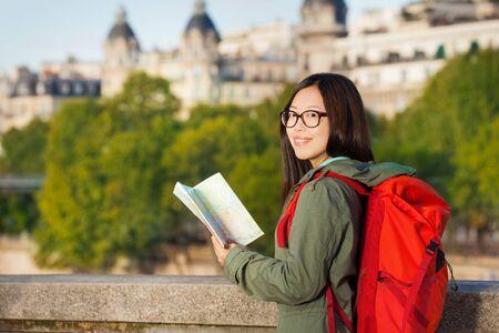 mochila de viaje: Chica joven que recorre a lo largo del Sena con el mapa de París Foto de archivo