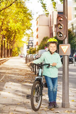 Boy waiting for green traffic light with his bike
