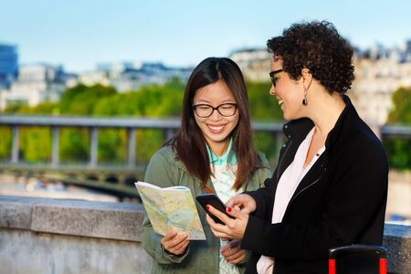 guide: Women tourists holding a paper map and smart phone