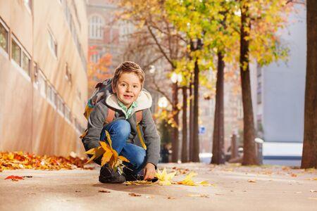 feuille arbre: érable garçon mignon collecte laisse sur son chemin de la maison