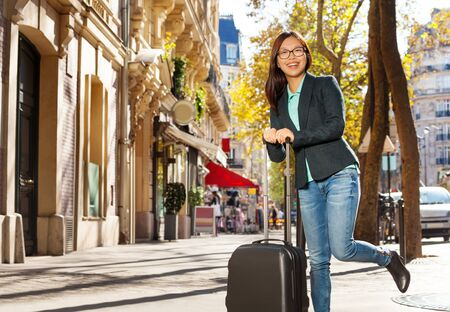 people travelling: Happy traveler with suitcase on the street