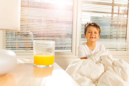 bedhead: Happy boy starting his morning with glass of juice