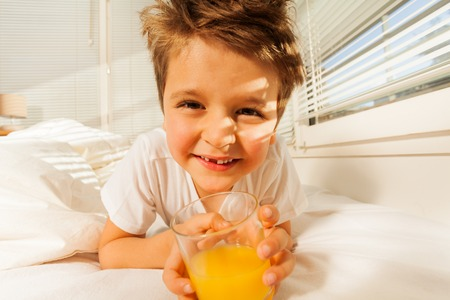 bedhead: Happy boy with glass of fresh juice in his bedroom Stock Photo