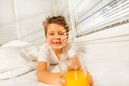 bedhead: Happy boy with glass of juice in sunny morning Stock Photo