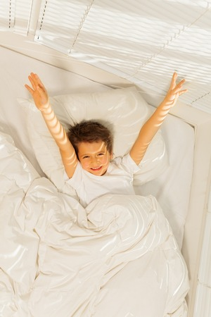 peppy: Peppy kid boy waking up in his white bedroom Stock Photo