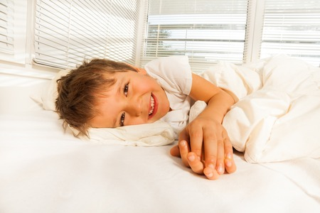 bedhead: Smiling boy lying in his bed looking at camera