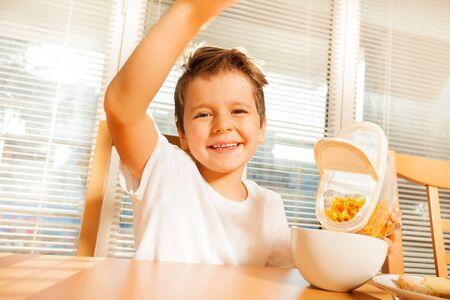 Happy boy making breakfast in the kitchen