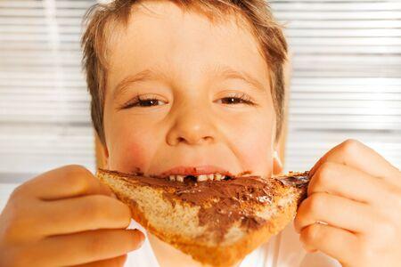 niños comiendo: muchacho niño feliz comiendo tostadas con crema de chocolate