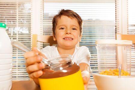 Portrait of happy kid boy with chocolate spread