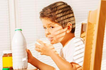 tomando leche: Little boy drinking milk during breakfast Foto de archivo