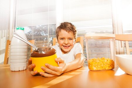 Happy boy holding glass can with chocolate spread Stock Photo