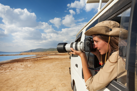 Girl taking photo from the window of safari jeep Stockfoto