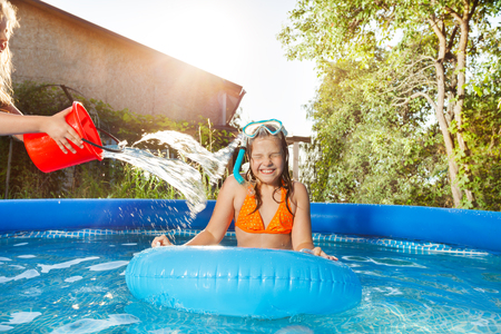 Girls pouring water from a red bucket in the pool Stock Photo