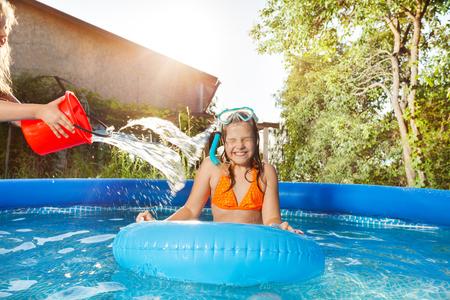 Meisjes gieten van water uit een rode emmer in het zwembad Stockfoto