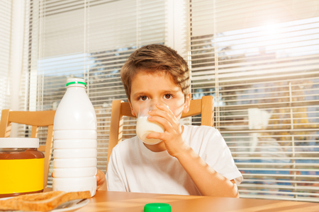 Little boy drinking milk at breakfast in kitchen Stock Photo