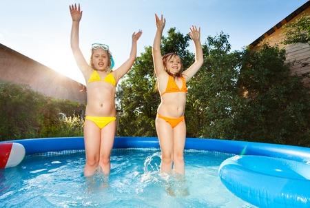 スイミング プールで楽しい 2 つの幸せな女の子