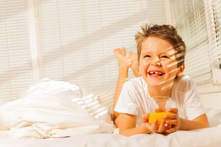 Smiling boy laying in his bed with orange juice Stock Photo