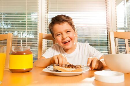 Happy boy spreading chocolate on his toast
